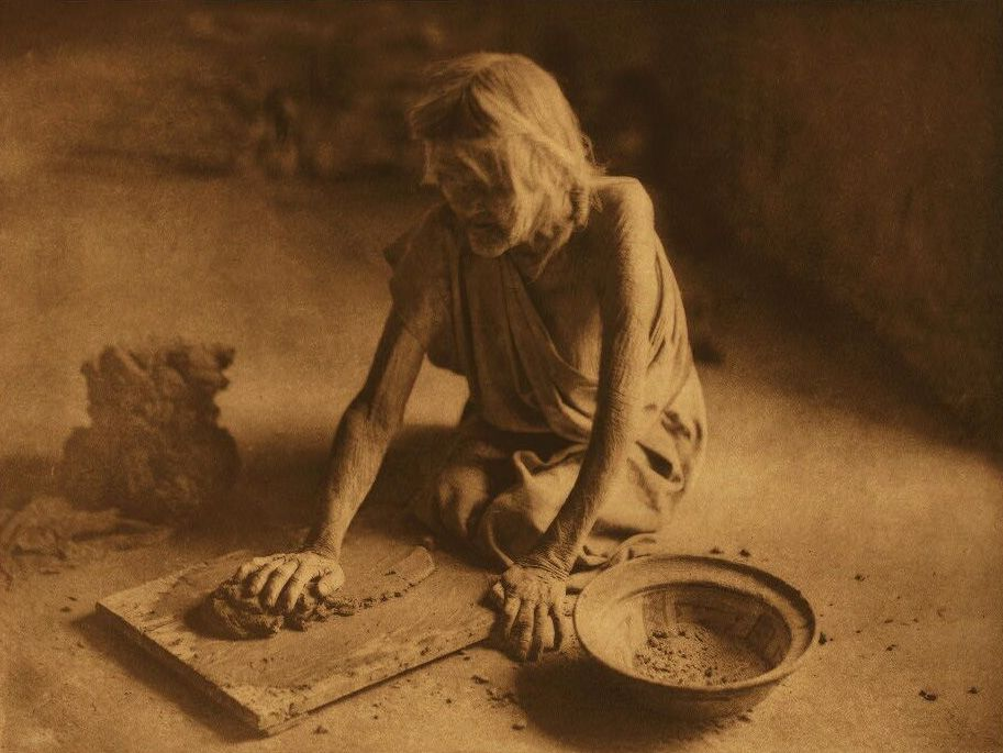 A Photograph of a Potter Mixing Clay.