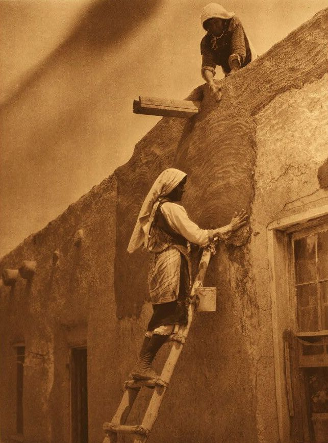 A Photograph of an American Indian Replastering a Paguate House.