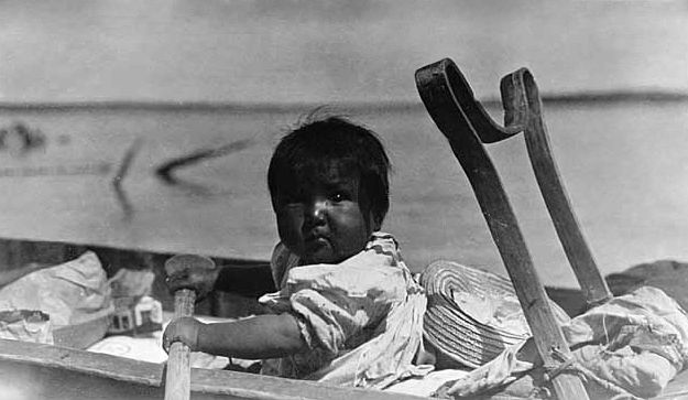 Indian Baby in a Canoe at Rainy Lake.