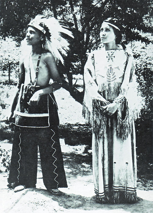 An old photograph of a Cherokee Boy and Girl in Traditional Dress on a North Carolina Reservation.