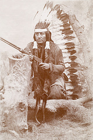 An old photograph of a Kiowa Indian with a Winchester Rifle c1880's.