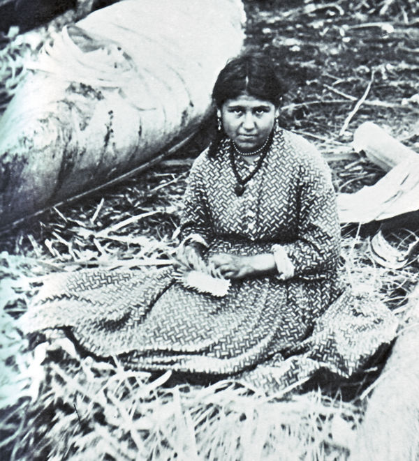 An old photograph of a Mohawk Woman Weaves a Basket Before a Birch Canoe.