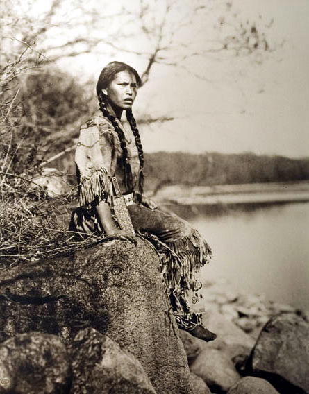 An old photograph of a Native American Girl Wearing a Beaded Buckskin Dress.