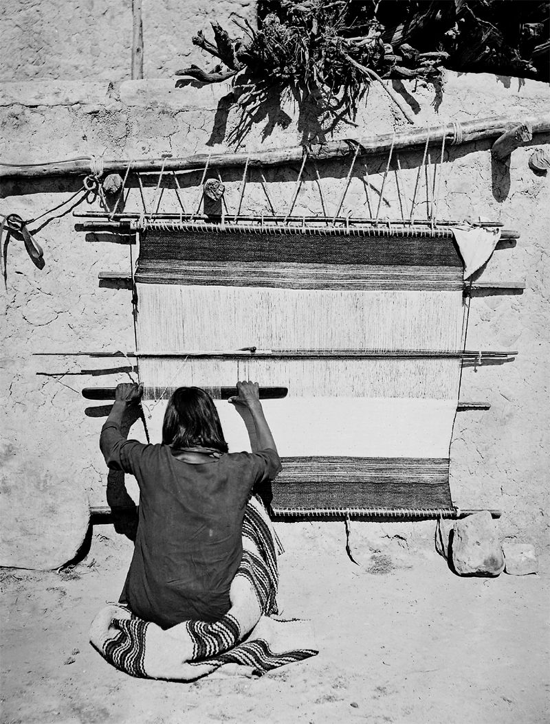 An old photograph of a Navaho Woman Weaving at Loom.