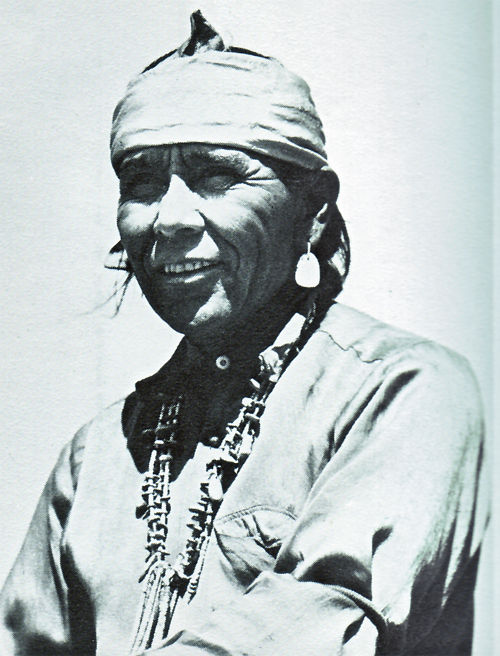 An old photograph of a Navajo Man Wearing a Turquoise Necklace, Earrings and Headband.