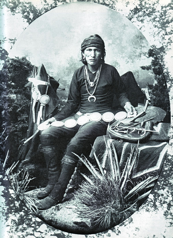 An old photograph of a Navajo Silversmith Displaying His Work.