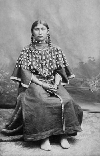 An old photograph of a Young Shoshone Woman Wearing Dress Decorated with Elks Teeth.