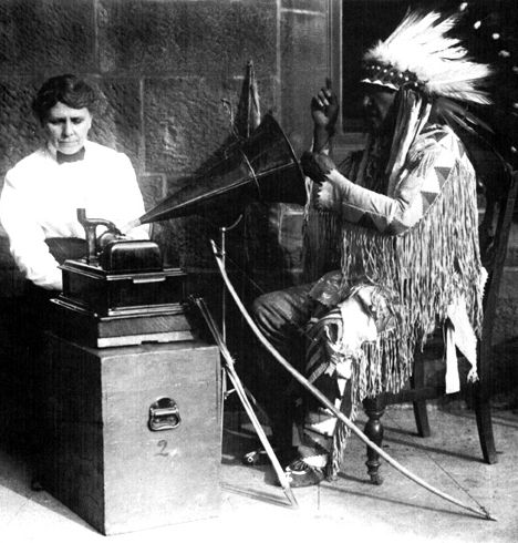 An old photograph of Alice Cunningham Fletcher with an Indian Recording Music.