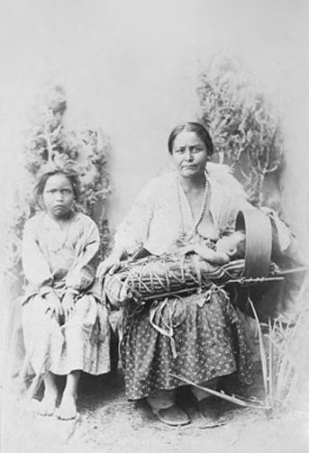 An old photograph of an Apache Mother, Child and Infant.
