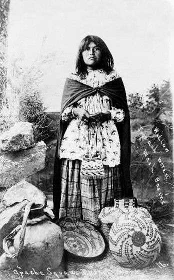 An old photograph of an Apache Squaw with Baskets.