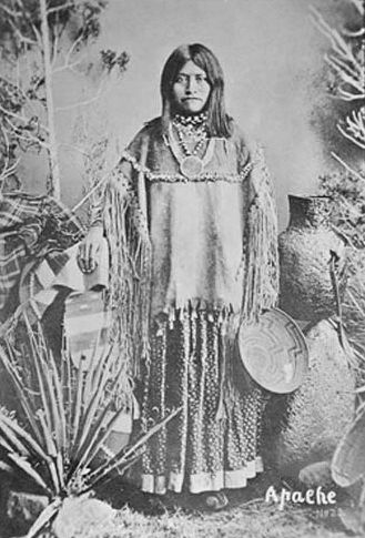 An old photograph of an Apache Woman Wearing a Classic Hide Blouse with Tin Cone Decorations.