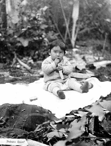 An old photograph of a Baby Native American Seated on a Blanket.