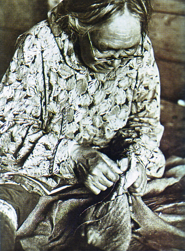 An old photograph of an Elderly Indian Woman Sewing Skins into Garments.