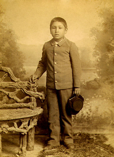 An old photograph of an Indian Boy in Government School Clothes.