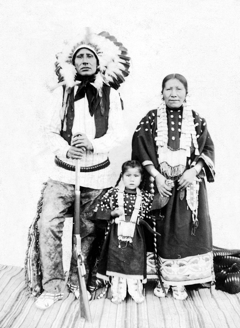 An old photograph of Little Chief with His Wife Minnie and Son in Native Dress.