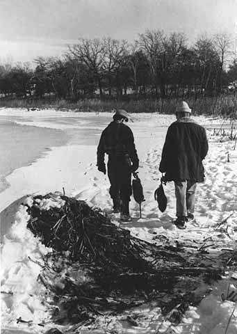 An old photograph of Men Carrying Two Recently Trapped Muskrats.