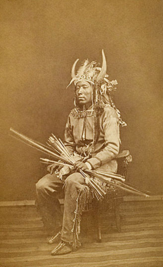 An old photograph of Mo-he - A Quahada Comanche Man in War Regalia.