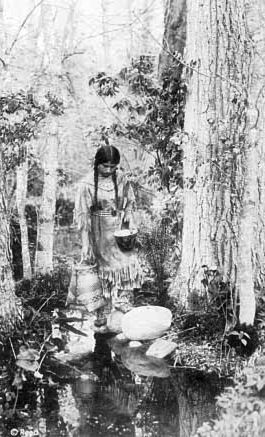 An old photograph of an Ojibwa Woman Carrying Water.