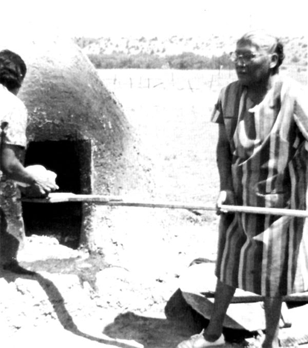 An old photograph of Pueblo Indians Baking Bread in a Horno.