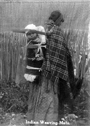 An old photograph of a Native American Woman Weaving Rush Mats at Mille Lacs with a Baby in a Cradle on her Back.