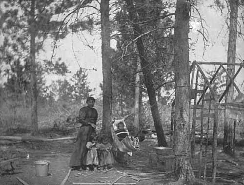 A Chippewa Indian Camp with Woman and Children.