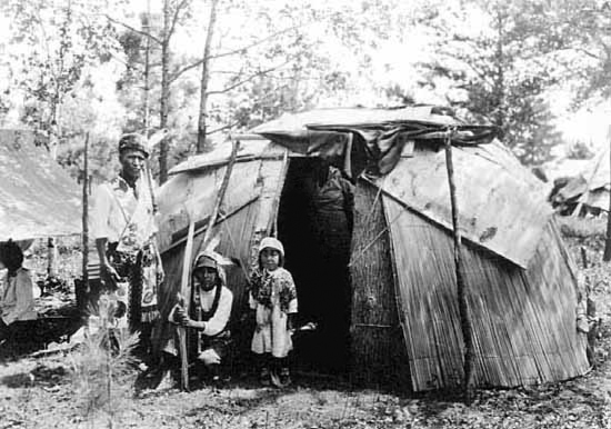 Chippewa Family Standing in Front of Birch Bark and Reed Wigwam.