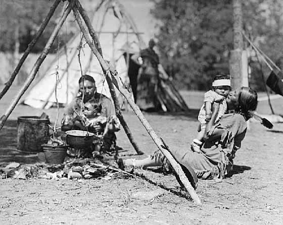 Women and Children Seated by a Camp Fire in Chippewa Village, Itasca State Park.