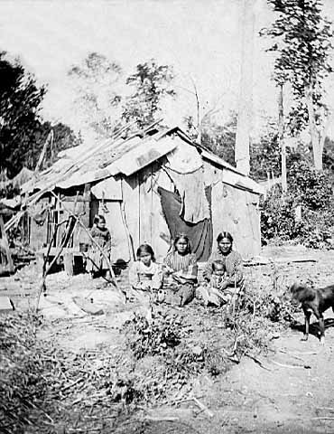 Chippewa Woman and Children Seated in Front of a Wigwam.